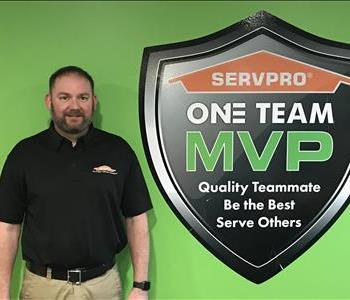 Owner standing next to SERVPRO MVP One Team Signage