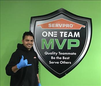 Male Employee with dark hair standing in front of a SERVPRO One Team sign.